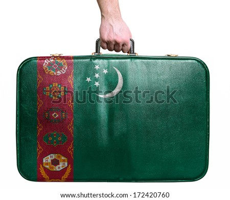 Tourist hand holding vintage leather travel bag with flag of Turkmenistan - stock photo