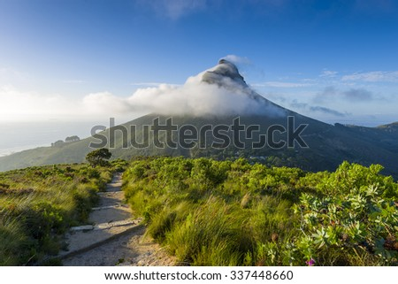 Tourist hikers up Cape Town, Table Mountain landscape, overlooking Lions Head peak - stock photo