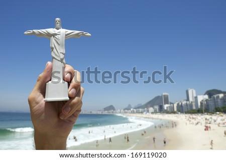 Tourist holding Corcovado Christ the Redeemer statue souvenir at sunny view of Copacabana Beach Rio de Janeiro skyline Brazil - stock photo