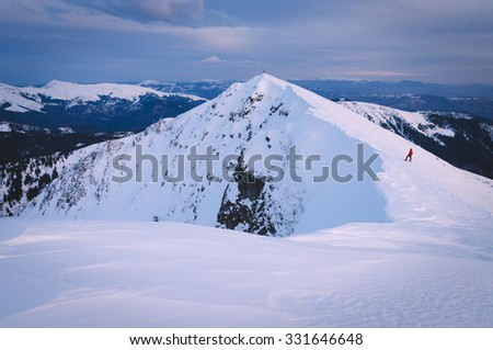 Tourist in a red jacket on the mountain. Winter landscape in the morning. Carpathians, Ukraine, Europe. Color toning - stock photo