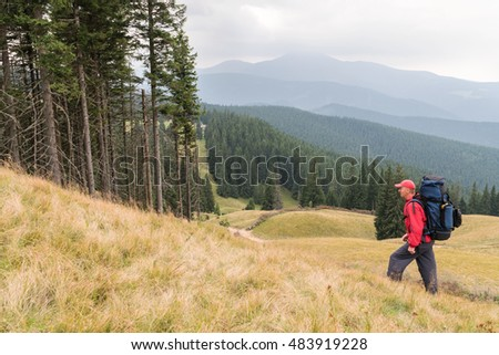 Tourist in a red track suit and a cap with a backpack on his back goes through the woods in the mountains