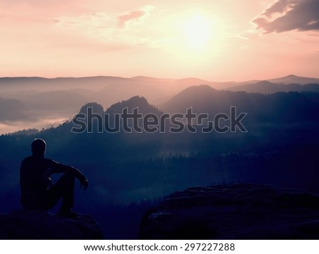 Tourist in black wind jacket sit on sharp rock and watching into misty valley bellow.  - stock photo