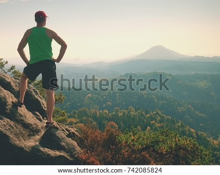 Tourist in green singlet and black shorts on a rock, enjoy spring nature  scenery. Long valley in sun bath full of creamy fog
