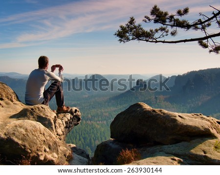 Tourist in grey t-shirt takes photos with smart phone on peak of rock. Dreamy hilly landscape below, spring orange pink misty sunrise in a beautiful valley below rocky mountains. - stock photo