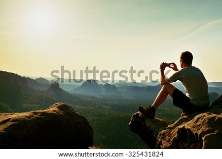 Tourist in grey t-shirt takes photos with smart phone on peak of rock. Dreamy hilly landscape below, spring misty sunrise  - stock photo