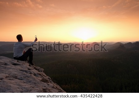 Tourist in grey t-shirt takes photos with smart phone on peak of rock. Dreamy hilly landscape below, spring orange pink misty sunrise in beautiful valley below rocky mountains. Hiking man taking photo