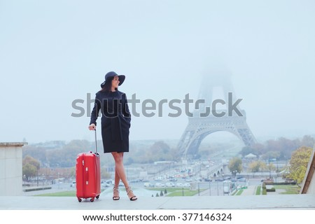 tourist in Paris, Europe tour, woman with luggage near Eiffel Tower, France - stock photo