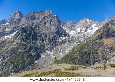 Tourist in yellow jacket enjoy beautiful view in the high mountains, Italian Alps