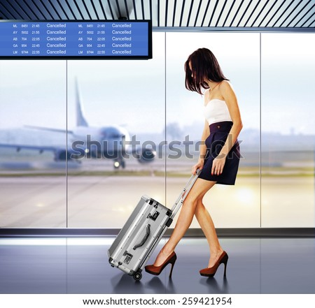 tourist info signage in airport and beautiful passenger with luggage - stock photo