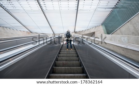 Tourist inside metro station on escalators. Lisbon, Portugal. - stock photo