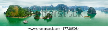 Tourist junks floating among limestone rocks at early morning in Ha Long Bay, South China Sea, Vietnam, Southeast Asia. Ten vertical images panorama - stock photo