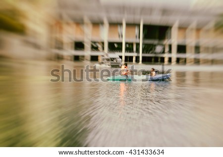 Tourist kayaking in the pond or lake with radial blur in Wachirabenchatat Park - stock photo