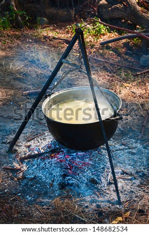 Tourist kettle above a fire with fish soup  - stock photo