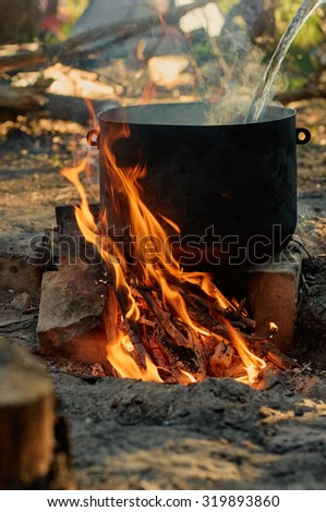 Tourist kettle on camp fire.  runing water