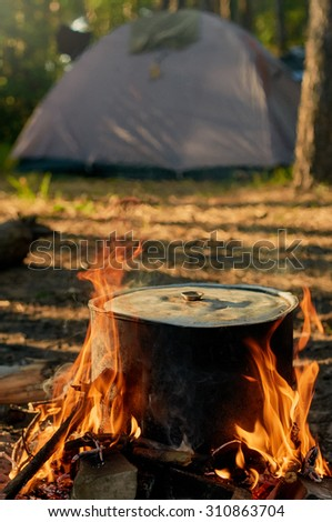 Tourist kettle on camp fire with tent on background