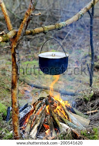 tourist kettle on campfire in forest - stock photo