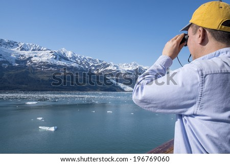 Tourist Looking at Glaciers and Mountains Through a Binocular  - stock photo