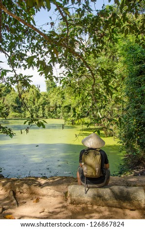 Tourist looking at the moat in Banteay Kdei Temple, Angkor, Cambodia