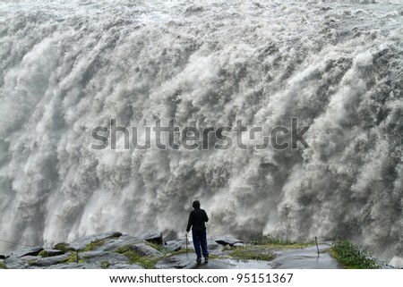 Tourist looking at the powerful waterfall of Dettifoss at Jôkulsargljufur in Vatnajökull National Park, Iceland - stock photo