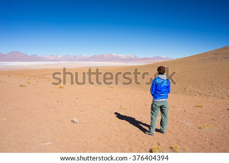 Tourist looking at view. Barren mountain range and desert on the highlands of the Andes on the way to the famous Uyuni Salt Flat, among the most important travel destination in Bolivia. - stock photo
