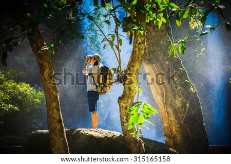Tourist looking through binoculars considers wild birds in the Khaoyai national park Thailand, water spray spreading around her - stock photo