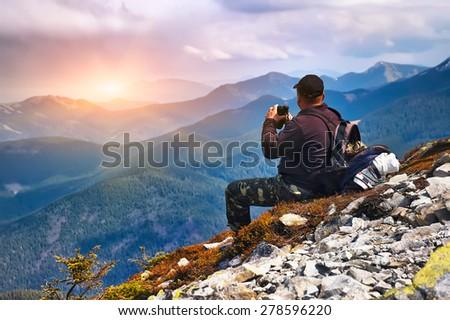 Tourist looking through binoculars sunset in the mountains - stock photo