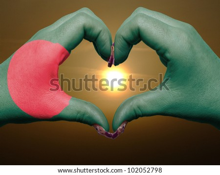Tourist made gesture  by bangladesh flag colored hands showing symbol of heart and love during sunrise - stock photo