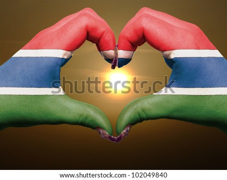 Tourist made gesture  by gambia flag colored hands showing symbol of heart and love during sunrise - stock photo