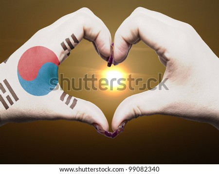 Tourist made gesture  by south korea flag colored hands showing symbol of heart and love during sunrise