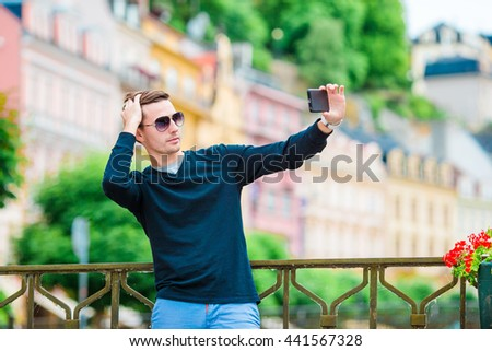 Tourist man taking travel photos with smartphone on summer holidays. Young attractive tourist taking selfie photo with mobile phone outdoors enjoying holidays travel destination in tourism and - stock photo