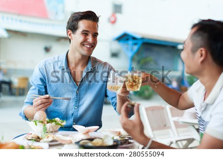 Tourist Men Cheers Toast Drink, Asian Mix Race Friends Guys Happy Smile Sitting at Cafe Eating Asian Food Street Local Cafe - stock photo