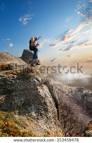 Tourist on a high rock at sunrise
