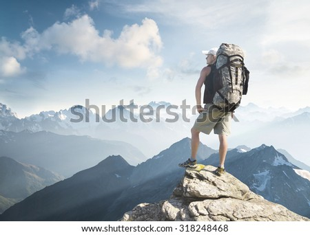 Tourist on the peak of high rocks. Sport and active life concept - stock photo
