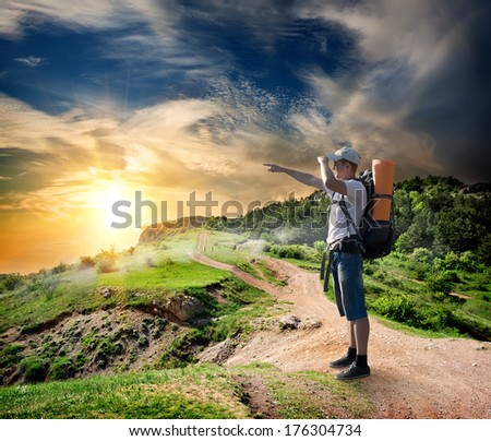 Tourist on the road in mountains at sunset