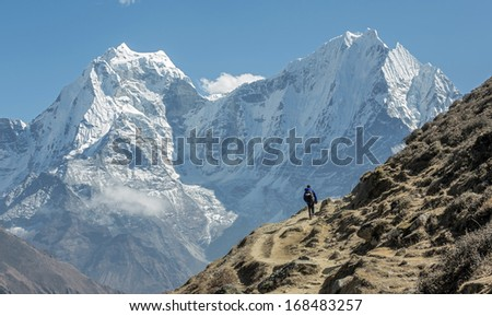 Tourist on the track in the background of Khantega and Thamserky peaks - Everest region, Nepal, Himalayas