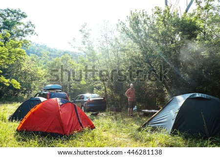 Tourist orange and green tents and cars in forest at campsite. Camping place in the meadow on nature in summer. Adventure travel active lifestyle outdoor background. Family time holidays. - stock photo