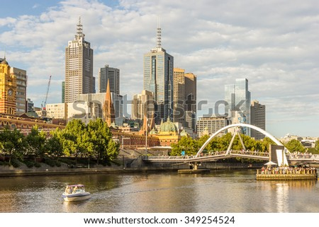 Tourist people Speedboat Ferry cruise Yarra River with Melbourne Skyline CBD Cityscape, Ponyfish Island from Southbank background under Cloudy Blue Sky at Golden Sunset in Summer Daytime, Australia