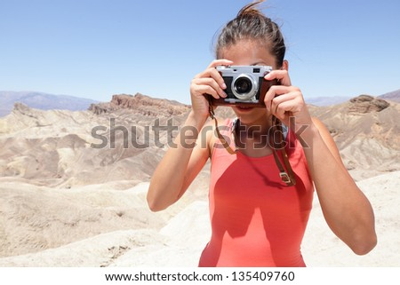 Tourist photographer woman taking pictures photo in Death Valley desert landscape of Zabriskie Point in Death Valley National Park, California, USA. Young woman on travel in United States. - stock photo