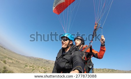 Tourist playing paragliding guided by a pilot - stock photo