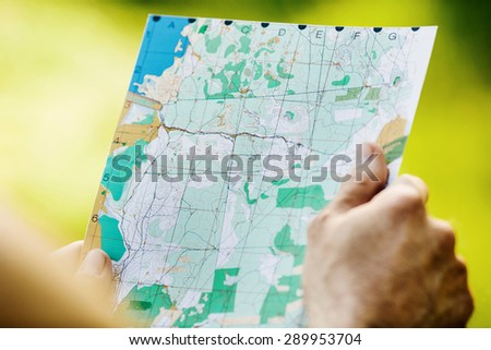 tourist reading a geographic map choosing best trails - stock photo