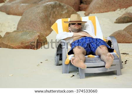 Tourist resting on a lounger. Sandy beach at the shores of India