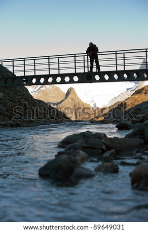 tourist resting on the bridge and admiring view in mountains