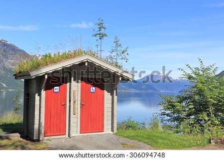 Tourist restroom at a rest area next to a fiord in Norway. Hardangerfjord area. - stock photo