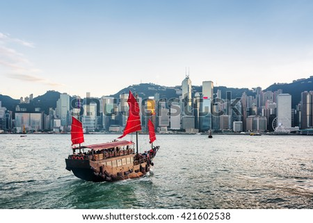 Tourist sailboat crosses Victoria harbor from Kowloon side to the Hong Kong Island. Scenic view of traditional Chinese wooden sailing ship with red sails. Skyscrapers of downtown in background. - stock photo