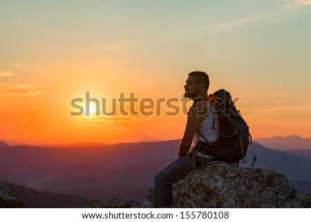 tourist sits in the mountains enjoying the sunrise - stock photo