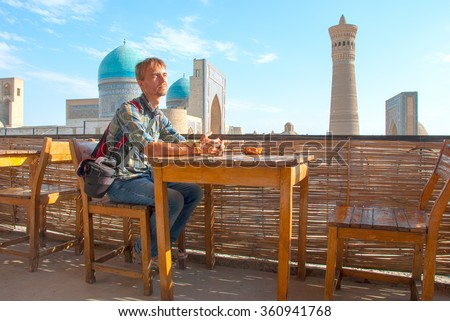 Tourist sitting in a roof-teahouse in the old city of Bukhara overlooking the complex Poi Kolon (UNESCO world Heritage), Uzbekistan, Central Asia. - stock photo