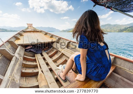 Tourist sitting on longtail boat sailing across the huge Cheow Lan lake in Khao Sok National Park, Thailand - stock photo