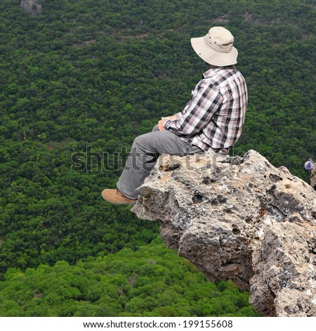 Tourist sitting on the rock over an abyss and looking at wood - stock photo