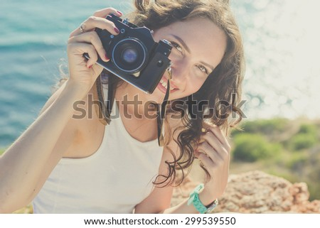 Tourist smiling slim girl making photo by old camera on the peak of mountain over sea background - stock photo