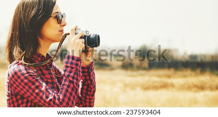 Tourist smiling young woman takes photographs with vintage old photo camera in spring outdoor - stock photo
